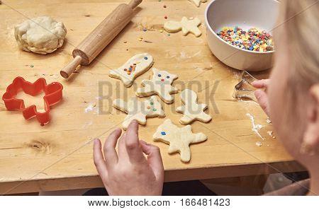 Little girl preparing Christmas cookies using cookie cutter