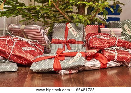 Celebration of New Year at home. Many gifts lying under Christmas tree.