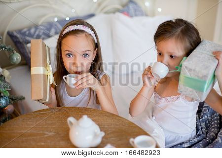 Child girls wake up in her bed near decorated Christmas tree in beautiful room in the holiday morning, have breakfast