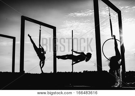 Beautiful Dancers Silhouettes Performing Aerial Dance On Roof At Sunset