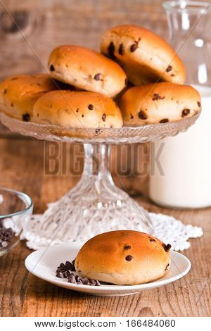 Chocolate chip brioche bun on wooden table.