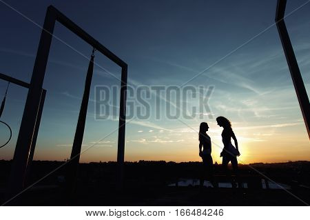 Two Beautiful Dancer Silhouettes Posing On Roof At Sunset