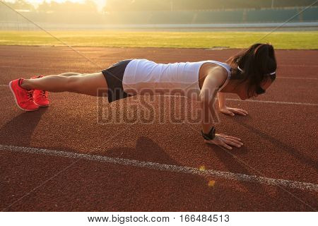 young fitness woman runner doing push ups on stadium track
