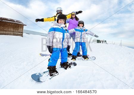 Happy family of mother, father and two songs snowboarders having fun at ski resort