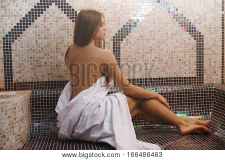 Sexy topless girl wraped in a bedsheet sitting near tiled wall with her back to viewer in sauna