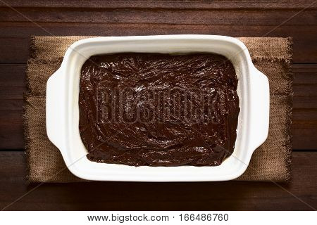 Basic homemade brownie or chocolate cake dough in greased and floured baking pan photographed overhead on dark wood with natural light