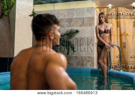 Sexy blonde staying in luxurious swimming pool. Young attractive tatooed man is looking at her close up shot from his back