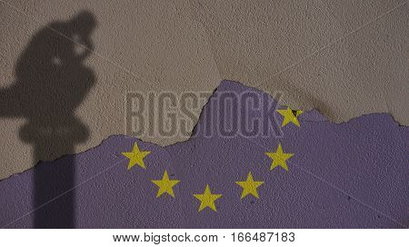 Thinker Shadow on Europe Flag and Grey Plaster Concrete Wall