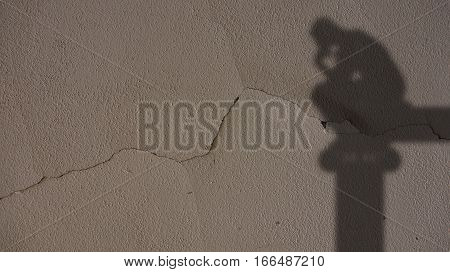 Thinker Shadow on Grey Cracked Concrete Wall