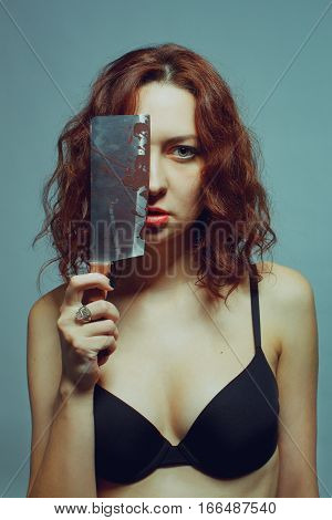 Seductive naked girl posing with chopper over blue background