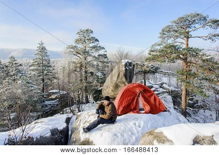 Male Climber Nearly His Tent On The Top Of Rock