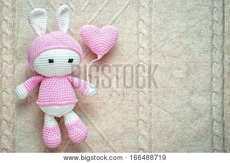 Crochet Children's Soft Toy Bunny Wielding Knitted Balloon On The Patterned Knit Background, With Co