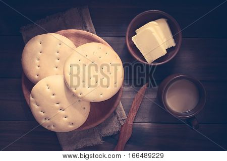 Traditional Chilean Hallulla bread rolls on wooden plate with butter and coffee with milk on the side photographed overhead on dark wood with natural light (Digitally Altered: Toned Image)