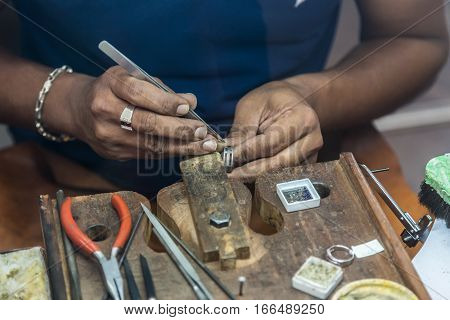 Jeweler making handmade jewelry on vintage workbench. Craft of jewelery making. Repairing ring by inlaid tight gem.
