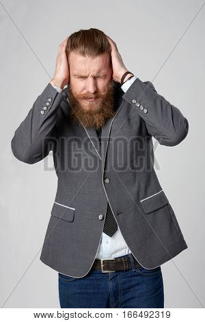 Discontent stressed hipster business man holding his head in hands