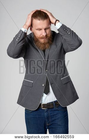 Frustrated stressed hipster business man holding his head in hands