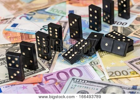 dominoes on euro and dollar banknotes. close up