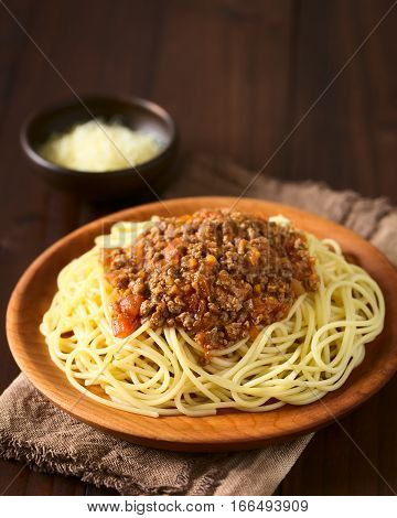 Spaghetti with homemade bolognese sauce made of fresh tomato mincemeat onion garlic and carrot served on wooden plate with grated cheese in the back photographed with natural light (Selective Focus Focus on the front of the sauce)