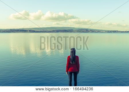 Woman stands on the lake shore at the water's edge. On the sky light clouds. Further prospects.
