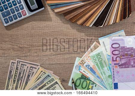 wooden sampler with money on wooden desk.