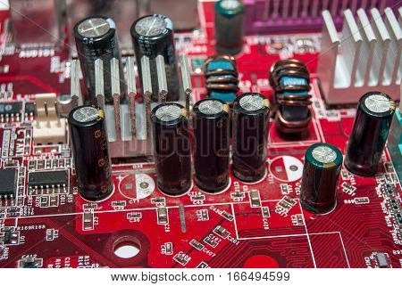 red computer motherboard with electrical components, macro