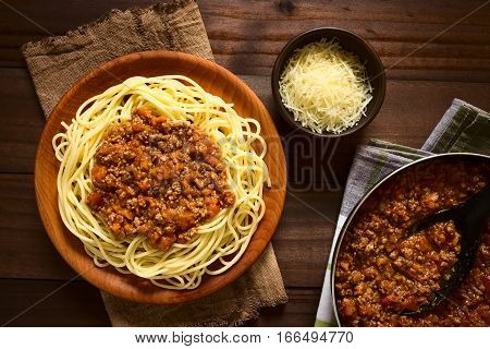 Spaghetti with homemade bolognese sauce made of fresh tomato mincemeat onion garlic and carrot served on wooden plate with grated cheese and skillet with sauce on the side photographed overhead with natural light