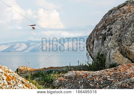 Hang glider flies over mountain lake view through stones