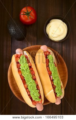 Chilean Completo Italiano (Italian) traditional hot dog sandwich made of bread sausage tomato and avocado mayonnaise in small bowl on the side photographed overhead on dark wood with natural light (Selective Focus Focus on the hot dog)