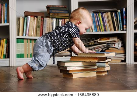 Eight months old todler baby playing with books on the floor