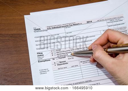 Woman hand filling income tax forms 1040