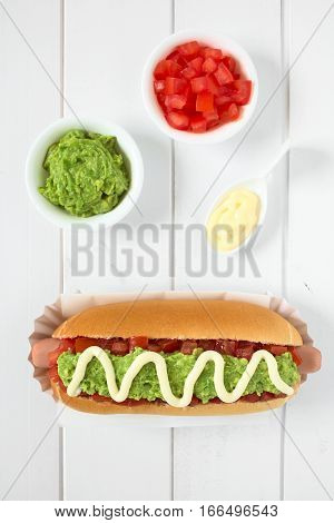 Chilean Completo Italiano (Italian) traditional hot dog sandwich made of bread sausage tomato avocado and mayonnaise ingredients on the side photographed overhead on white wood with natural light (Selective Focus Focus on the hot dog)