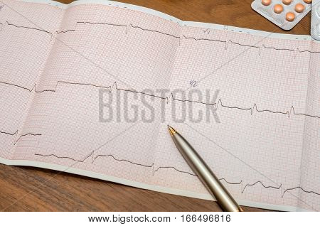Electrocardiogram graph report with pills on desk