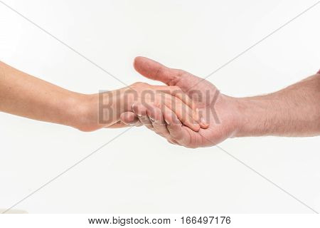 Close-up view of male hand carefully holding female hand on white