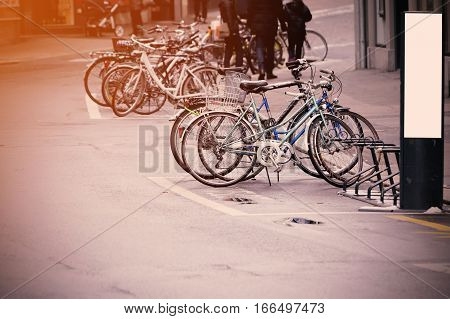 Group of bicycles parked at roadside in the city.
