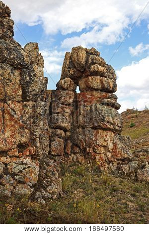 Unusual natural textured rock formations on sky background vertical