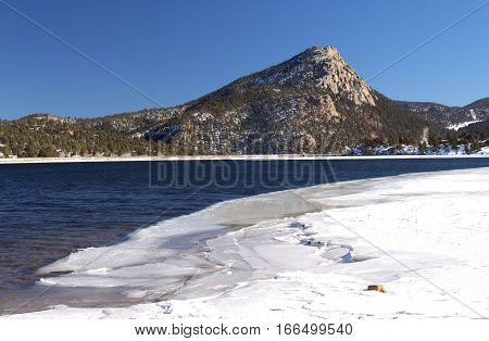 Looking across the partially frozen waters of Lake Estes at a prominent mountain peak in Colorado.