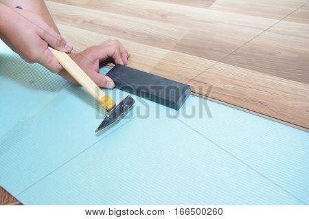 Man Installing New Laminate Wood Flooring. Worker Installing wooden laminate flooring with hammer. Handyman laying down laminate flooring boards while renovating a house.