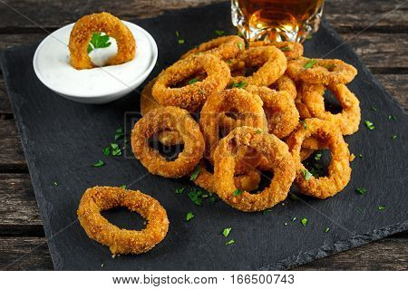 Fried Breaded Onion Rings with sauce and beer.