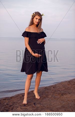 pregnant woman with long hair standing on the beach in a black dress at sunset