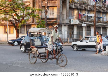 TOAMASINA MADAGASCAR - OCTOBER 17 2016: Traditional rickshaw bicycle with malagasy peoples in Madagascar second largest city Toamasina. Ordinary street life in Toamasina Madagascar October 17. 2016