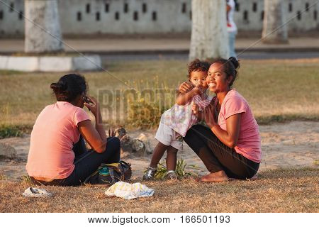 Malagasy Beauties, Woman With Child Resting In Park