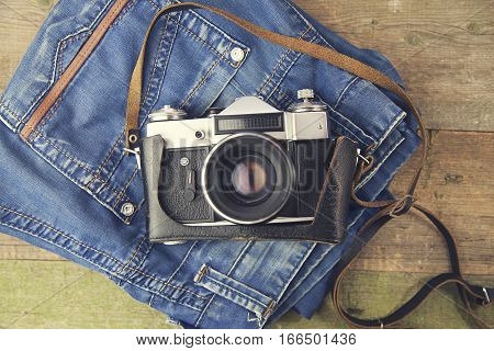 jeans and camera on wooden background table