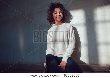 Beautiful African girl dressed in blank sweatshirt sitting on a gray background. Mock-up.