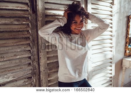 Beautiful African girl dressed in blank sweatshirt standing in the old style room. Mock-up.