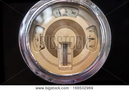 Old circular indicator with oil gauge temperature and fuel level. Isolated over black background