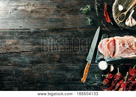 Loin with knife and spices on wooden cutting board