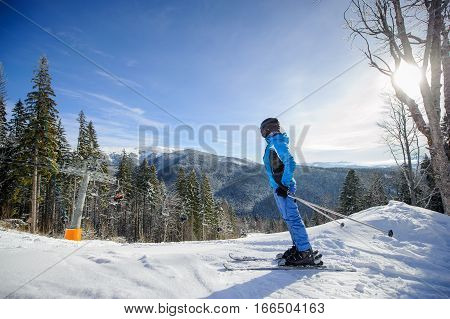 Female Skier Against Ski-lift And Winter Mountains Background