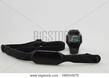 Watch and chest strap of a heart rate monitor on a white background