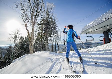 Female Skier On The Top Of Ski Slope With Ski-lift