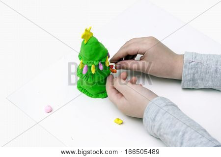 Children's hands mould a New Year tree from plasticine